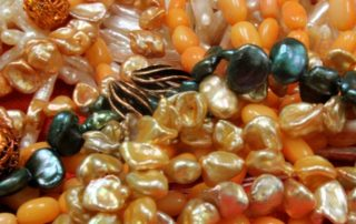 Some orange and gold polished beads that are available at The Twisted Bead & Rock Shop.