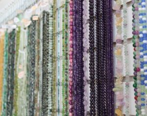 A selection of gemstones in shades of purple and green that are available at The Twisted Bead & Rock Shop.